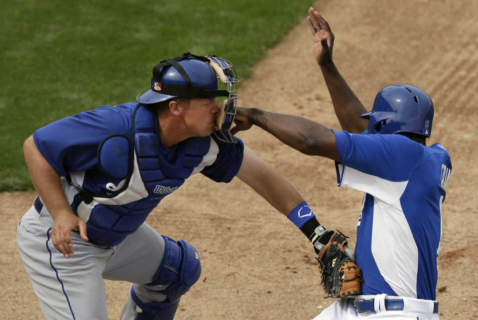 Los Angeles Dodgers catcher Tim Federowicz, left, gets fist to the mask as he tags out Kansas City Royals' Lorenzo Cain at home during the sixth inning in an exhibition spring training baseball game Wednesday, March 20, 2013, in Surprise, Ariz. (AP Photo/Gregory Bull)