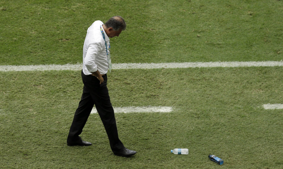 Photo - Iran coach Carlos Queiroz kicks a water bottle after Bosnia midfielder Miralem Pjanic's goal during the second half of a group F World Cup soccer match at the Arena Fonte Nova in Salvador, Brazil, Wednesday, June 25, 2014. (AP Photo/Themba Hadebe)