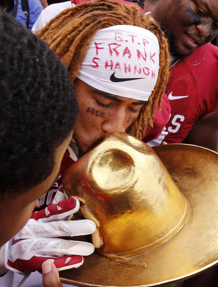 Photo - Oklahoma's Zack Sanchez kisses the Golden Hat Trophy after the Red River Showdown college football game where the University of Oklahoma Sooners (OU) defeated the University of Texas Longhorns (UT)  31-26 at the Cotton Bowl in Dallas, Texas on Saturday, Oct. 11, 2014. Photo by Steve Sisney, The Oklahoman