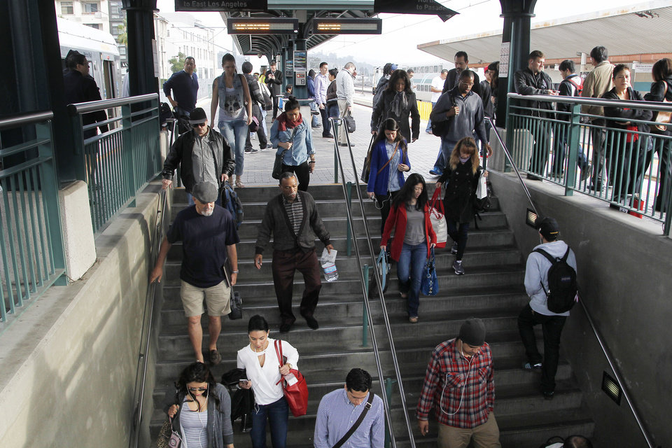 Photo - Pedestrians prepare to board a train at Union Station Friday March 7, 2014 in Los  Angeles. Americans are boarding public buses, trains and subways in greater numbers than any time since the suburbs began to boom. Nearly 10.7 billion trips in 2013, to be precise, the highest number since 1956.  (AP Photo/Nick Ut)