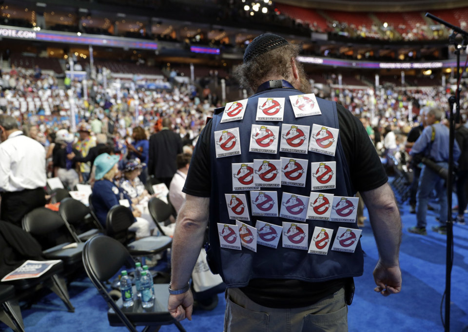 "Photo - A delegate walks around on the convention floor with buttons read, ""Trumpbusters"" before the start of the second day session of the Democratic National Convention in Philadelphia, Tuesday, July 26, 2016. (AP Photo/John Locher)"
