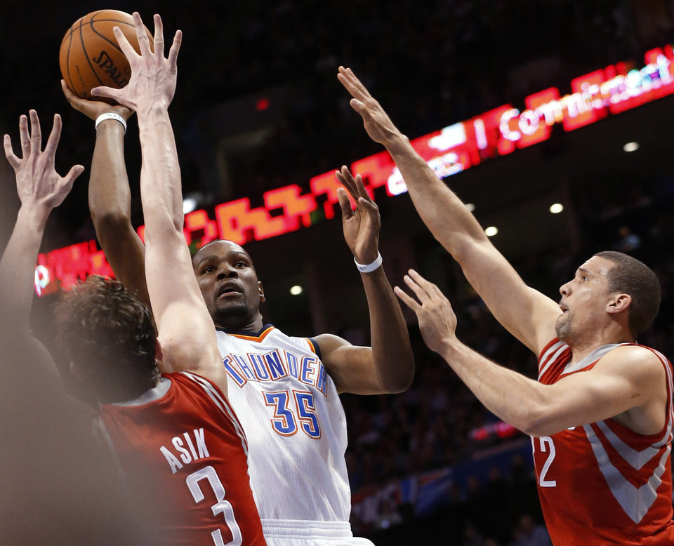 Photo - Oklahoma City Thunder forward Kevin Durant (35) shoots between Houston Rockets center Omer Asik (3) and guard Francisco Garcia (32) during the fourth quarter of an NBA basketball game in Oklahoma City, Tuesday, March 11, 2014. Oklahoma City won 106-98. (AP Photo/Sue Ogrocki)