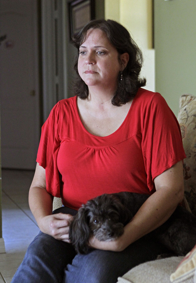 Photo -   In this Tuesday, July 31, 2012 photo, Marisol Walker sits with her dog in her home in Ocoee, Fla. Walker is fighting to keep the home that she and her husband bought about a year before his business collapsed. Walker says they haven't been able to pay the mortgage in 1½ years. She works part-time, while her husband is trying to restart his business. She finds the current political debate alienating.
