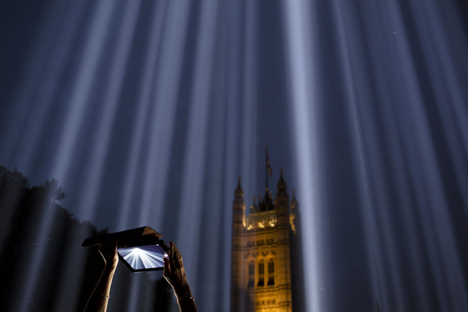 Photo - AP10ThingsToSee - A woman uses a tablet to photograph shafts of light piercing the night sky at an installation entitled