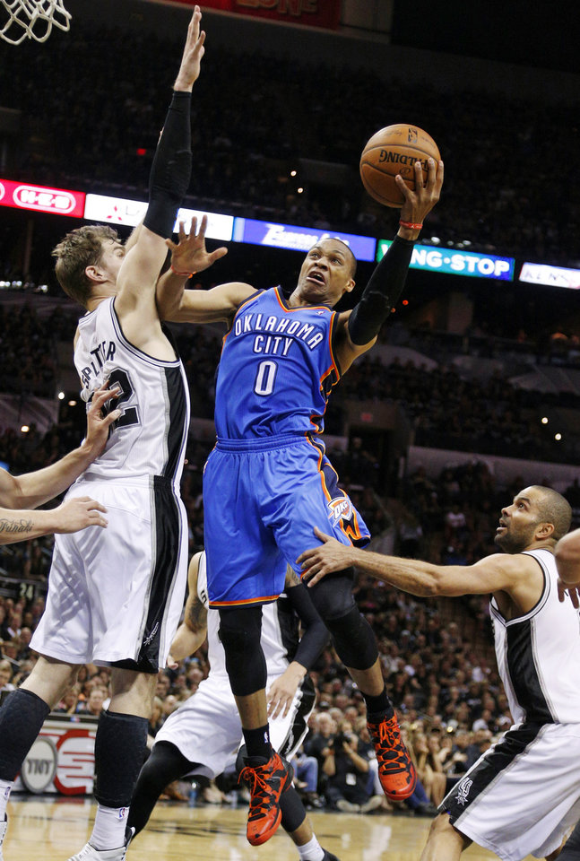 Oklahoma City's Russell Westbrook (0) takes the ball to the basket between San Antonio's Tiago Splitter (22) and Tony Parker (9) during Game 1 of the Western Conference Finals in the NBA playoffs between the Oklahoma City Thunder and the San Antonio Spurs at the AT&T Center in San Antonio, Monday, May 19, 2014. Photo by Sarah Phipps, The Oklahoman