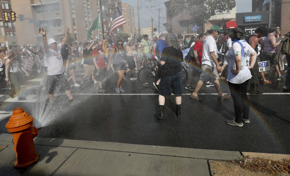 Photo - Supporters of Sen. Bernie Sanders, I-Vt., cool off in a fire hydrant during a march in downtown on Sunday, July 24, 2016, in Philadelphia. The Democratic National Convention starts Monday in Philadelphia. (AP Photo/Alex Brandon)