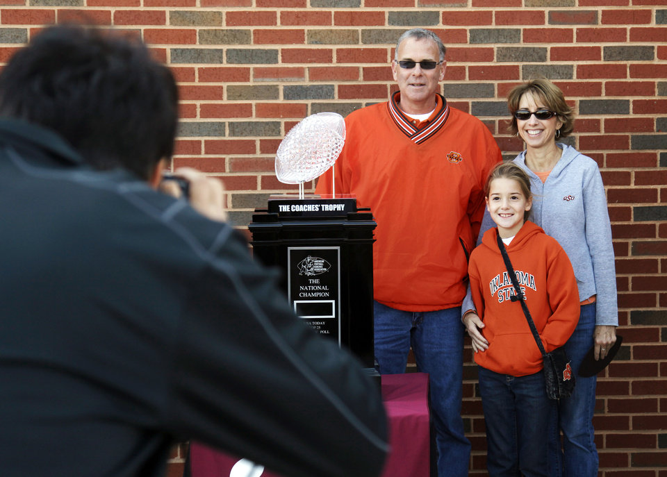 Photo - Roger Goodwin, Karla Goodwin and Macy Goodwin, 9, of Cherokee, Okla., pose for a photo with the BCS National Championship Coaches' Trophy before a college football game between the Oklahoma State University Cowboys (OSU) and the Baylor University Bears (BU) at Boone Pickens Stadium in Stillwater, Okla., Saturday, Oct. 29, 2011. Photo by Nate Billings, The Oklahoman