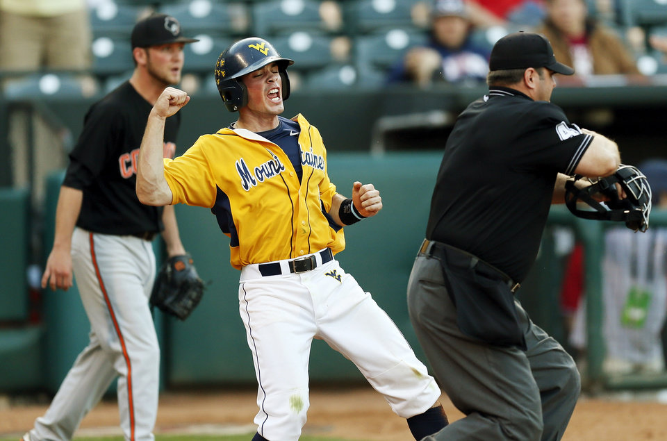Photo - West Virginia's Bobby Boyd (4) reacts in front of Oklahoma State pitcher Brendan McCurry (4) after being called safe by umpire Mike Morris on a slide at home plate to score the winning run in the tenth inning during an NCAA baseball game between Oklahoma State and West Virginia in the Big 12 Baseball Championship tournament at the Chickasaw Bricktown Ballpark in Oklahoma City, Saturday, May 25, 2013. WVU beat OSU 6-5 in ten innings. Photo by Nate Billings, The Oklahoman