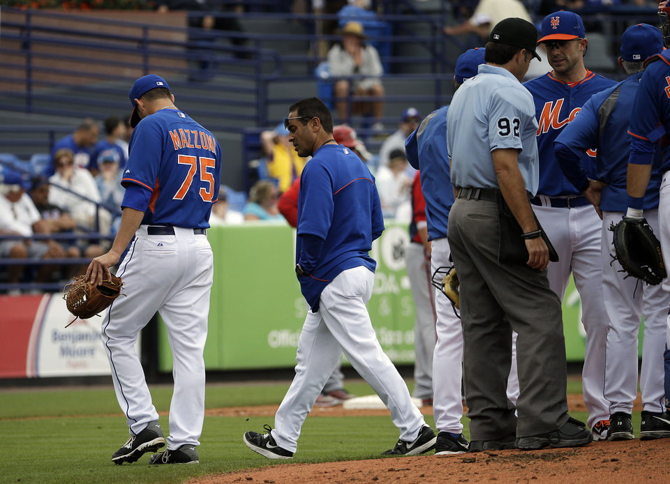 Photo - New York Mets starting pitcher Cory Mazzoni, left, leaves the field in the second inning of an exhibition spring training baseball game against the Washington Nationals, Thursday, March 27, 2014, in Port St. Lucie, Fla. (AP Photo/David Goldman)