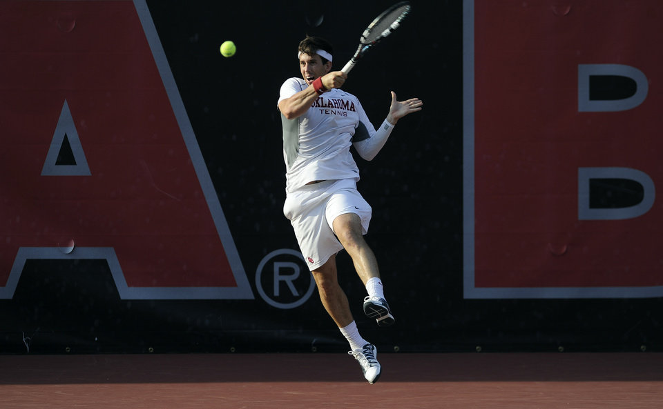 Photo - Oklahoma's Guillermo Alcorta returns a shot to Southern California's Connor Farren and Roberto Quiroz during a men's doubles match in the NCAA Division I team tennis championships, Tuesday, May 20, 2014, in Athens, Ga. (AP Photo/David Tulis)