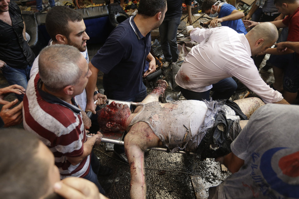Photo - EDITOR'S NOTE: GRAPHIC CONTENT -  Lebabnese citizens carry a body at the site of a car bomb explosion in southern Beirut, Lebanon, Thursday Aug. 15, 2013. The powerful car bomb ripped through a southern Beirut neighborhood that is a stronghold of the militant group Hezbollah on Thursday, killing people and trapping others in burning buildings, the media said. (AP Photo/Hussein Malla)