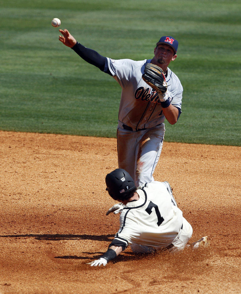Photo - Mississippi's Preston Overbey (1) throws to first for a double play as Vanderbilt's Dansby Swanson (7) slides into second base in the third inning during the Southeastern Conference NCAA college baseball tournament on Thursday, May 22, 2014, in Hoover, Ala. (AP Photo/Butch Dill)