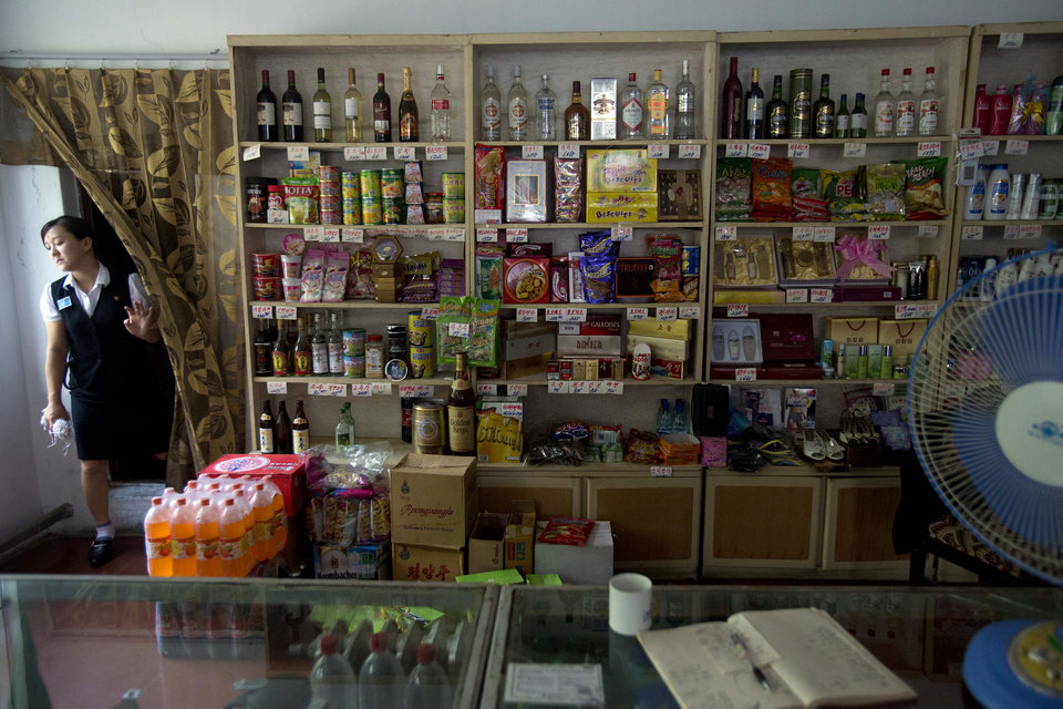 In this Aug. 11, 2012 photo, a shopkeeper steps out from the back room of a store open to foreigners in Hamhung, North Korea. (AP Photo/David Guttenfelder)