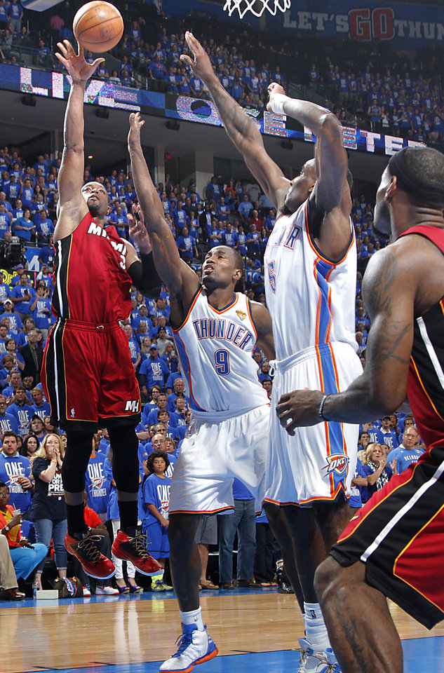 Oklahoma City's Serge Ibaka (9) and Kendrick Perkins (5) defend on Miami's Dwyane Wade (3) during Game 1 of the NBA Finals between the Oklahoma City Thunder and the Miami Heat at Chesapeake Energy Arena in Oklahoma City, Tuesday, June 12, 2012. Photo by Chris Landsberger, The Oklahoman