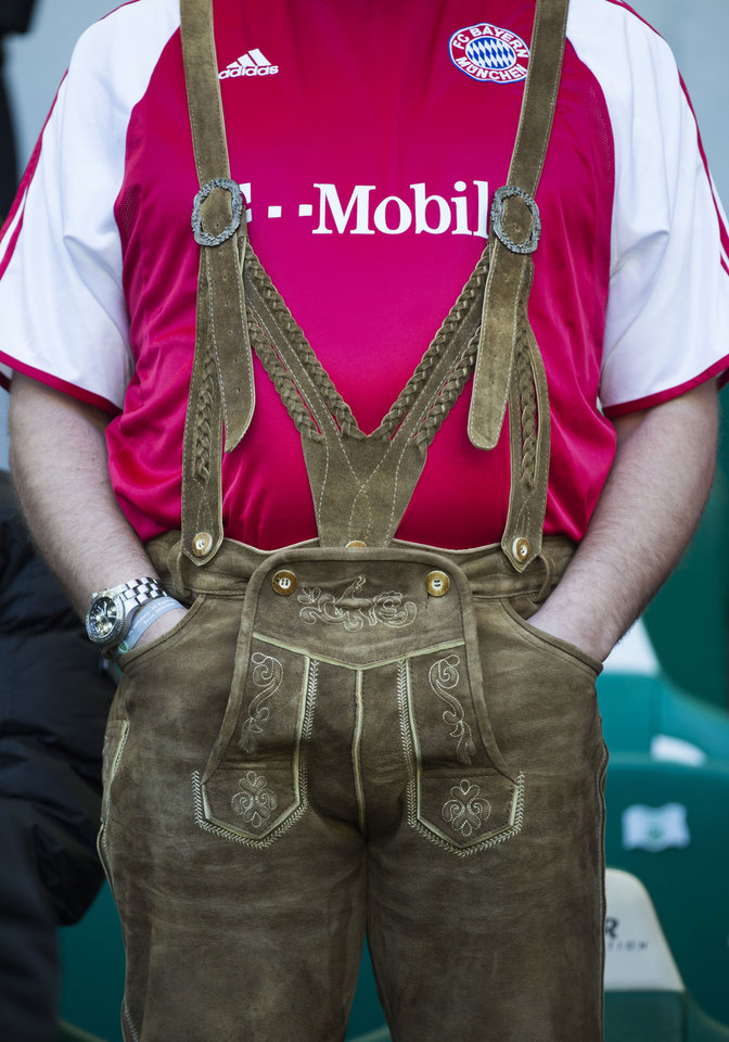 Photo - A supporter of Bayern Munich in traditional Bavarian clothes  waits for the start of the German Bundesliga soccer match between VfL Wolfsburg and Bayern Munich in Wolfsburg, Germany, Saturday, March 8, 2014. (AP Photo/Gero Breloer)