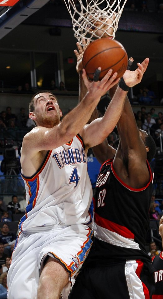Photo - Oklahoma City's Nick Collison (4) is fouled by Portland's Greg Oden (52) during the NBA basketball game between the Oklahoma City Thunder and the Portland Trail Blazers at the Ford Center in Oklahoma City, Friday, February 6, 2009. The Thunder won, 102-93. BY NATE BILLINGS, THE OKLAHOMAN