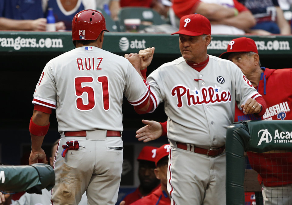 Photo - Philadelphia Phillies' Carlos Ruiz (51) is congratulated by manager Ryne Sandberg after scoring a run against the Texas Rangers during the first inning of a baseball game on Wednesday, April 2, 2014, in Arlington, Texas. (AP Photo/Jim Cowsert)