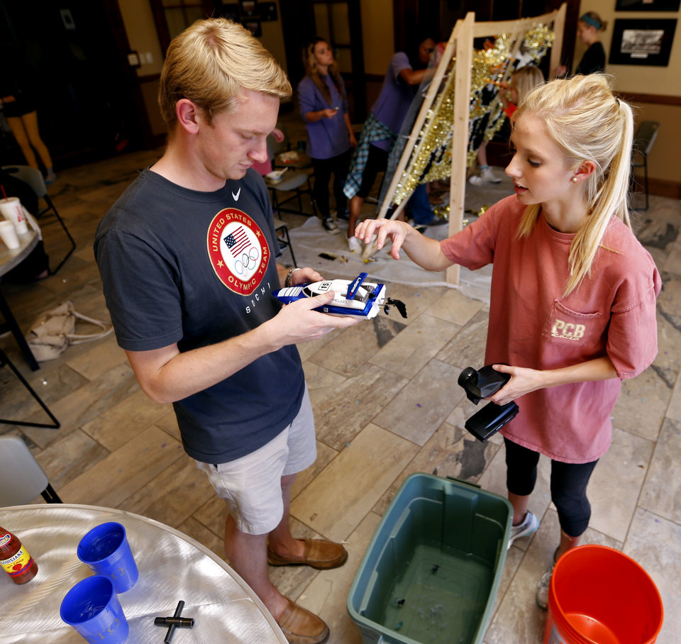 Photo -  University of Oklahoma students David Maxwell, Alpha Tau Omega, and Gamma Phi Beta member Sloan Carr work on props for their homecoming float. PHOTO BY STEVE SISNEY, THE OKLAHOMAN   STEVE SISNEY -