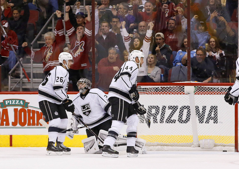 Photo - Los Angeles Kings' Jonathan Quick gives up a goal to Phoenix Coyotes' Oliver Ekman-Larsson, of Sweden, as Kings' Slava Voynov (26), of Russia, and Robyn Regehr (44), of Brazil, skate past Quick during the first period of an NHL hockey game Tuesday, Jan. 28, 2014, in Glendale, Ariz. (AP Photo/Ross D. Franklin)