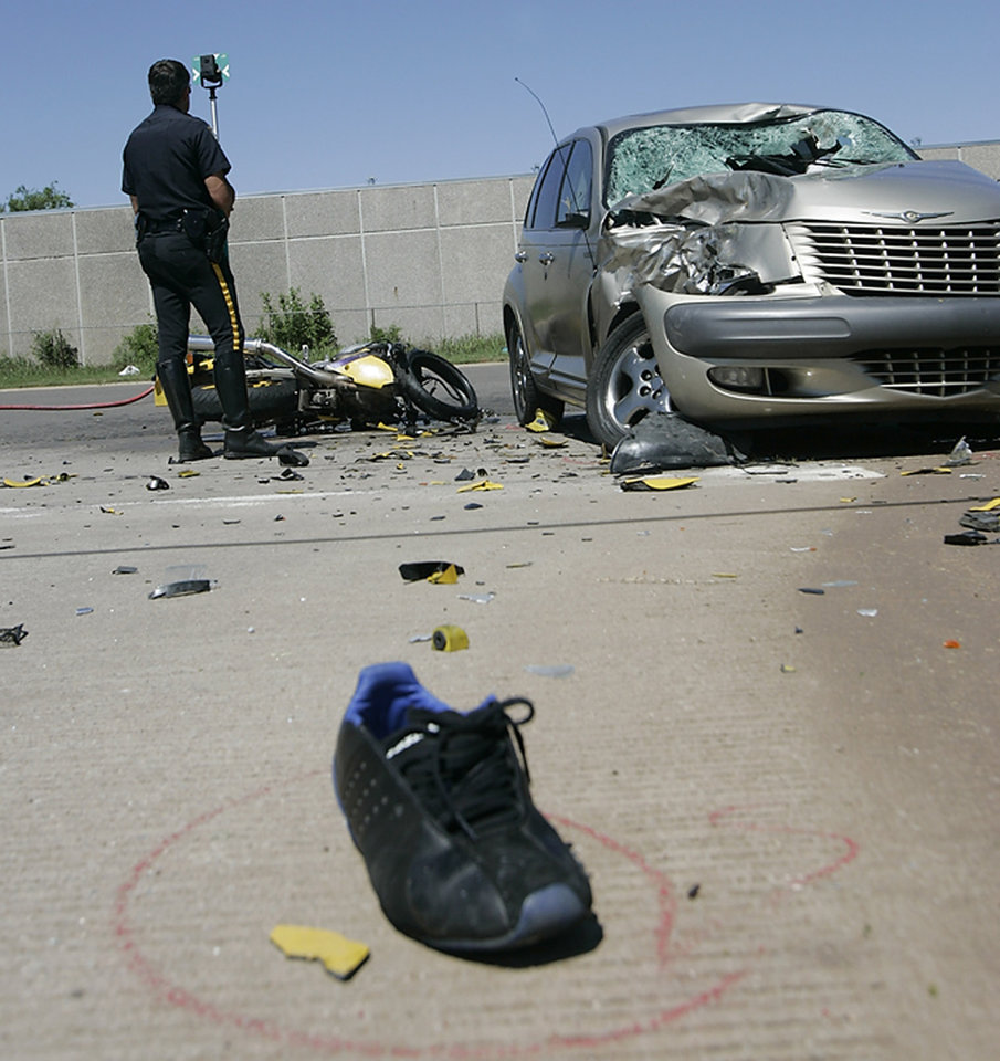 Midwest City police officer Sgt. Matt Mercer investigates a fatality accident involving a motorcycle and car near Sooner Road and Tina Drive in Midwest City Friday, May 29, 2009. Photo by Steve Gooch, The Oklahoman