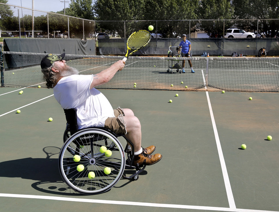 Photo -  Phillip Dalton sends the ball over the net to tennis pro Jenny Marcos during the veteran's wheelchair tennis clinic. [PHOTO BY JIM BECKEL, THE OKLAHOMAN]