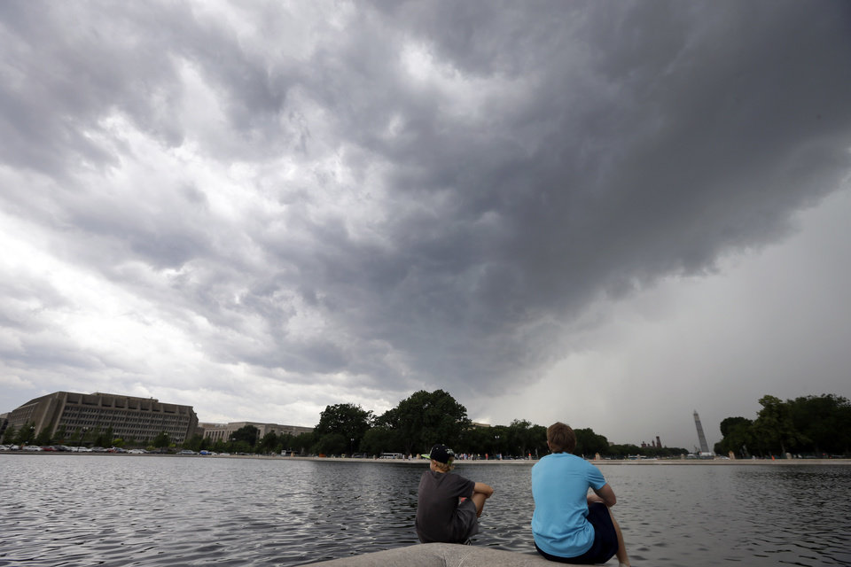 Photo - Kidwell Blanchard, left, 12, of Chandler, Ariz., sits with Andrew Sisk, 17, of Salt Lake City, Utah, as a storm moves through the area with the Washington Monument in the background, Thursday, June 13, 2013, in Washington. (AP Photo/Alex Brandon)