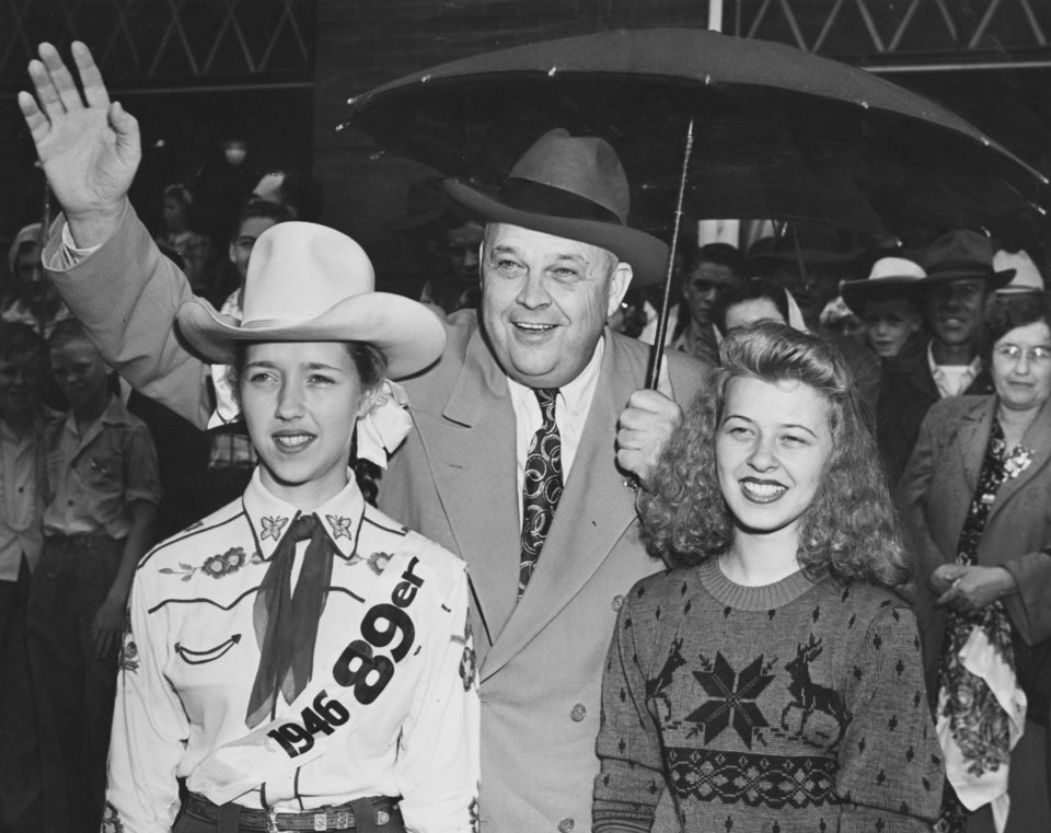 ROBERT S. KERR / OKLAHOMA GOVERNOR / GUTHRIE OKLAHOMA:  During the shower in Guthrie Monday morning Gov. Kerr went outside to see the 89er day parade.  Someone loaned him an umbrella and he graciously shared it with Mary Jane Emerick, left, the junior high-school parade queen, and Billie Roberts of Edmond.  Staff photo by Bill Stockwell.  Photo dated 04/22/1946.  Published on 04/22/1946 in The Oklahoma City Times.
