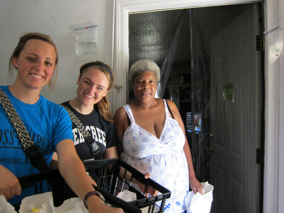 Photo - Chelsea Boyd, 21, and Abbey Stroder, 19, Quail Springs Baptist Church children's ministry interns, deliver free lunches to Gloria Roberts, a Terrace Apartments resident who said she planned to give the food to her grand children and youths at a nearby unit.  Carla Hinton - The Oklahoman