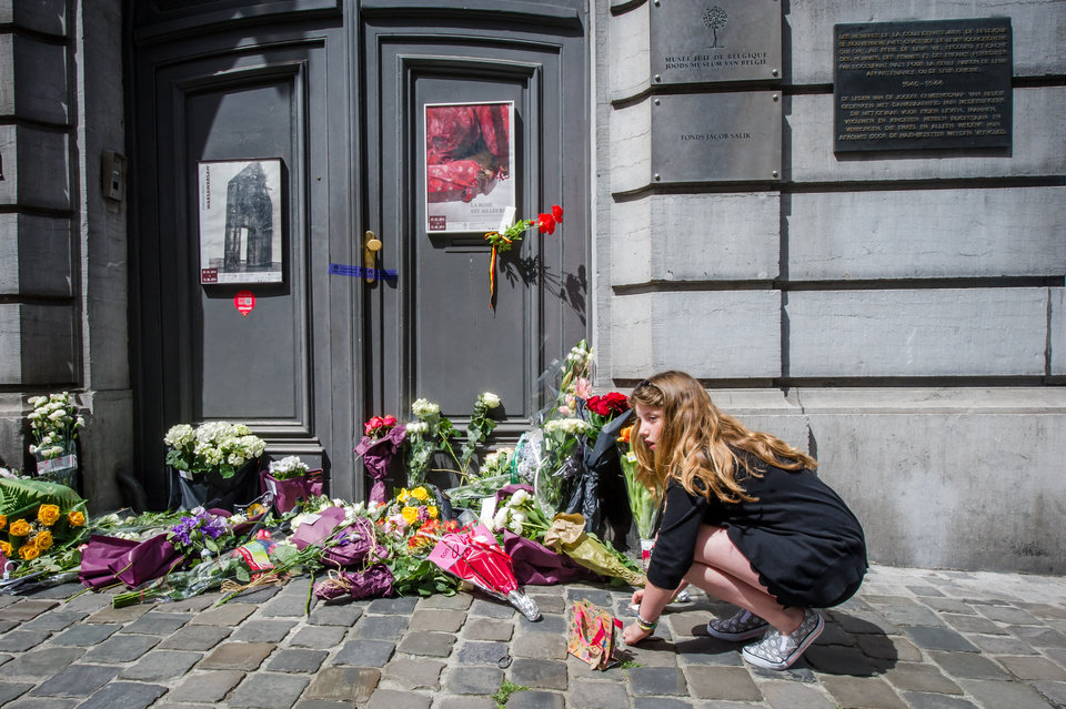 Photo - A girl lights candles at the Jewish Museum in Brussels, Sunday, May 25, 2014.  Police stepped up security at Jewish institutions, schools and synagogues after three people were killed and one seriously injured in a spree of gunfire at the Jewish Museum in Brussels on Saturday. (AP Photo/Geert Vanden Wijngaert)