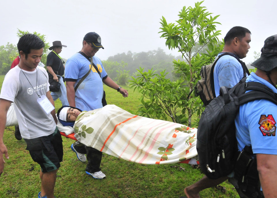 Photo - Police and rescuers carry Nicas Mabao Jr. to a waiting ambulance after surviving a steam-driven explosion of Mayon volcano, one of the Philippines' most active volcanoes, Tuesday May 7, 2013 in Albay province about 450 kilometers (285 Miles)southeast of Manila, Philippines. Mayon volcano rumbled to life Tuesday, spewing room-sized rocks toward nearly 30 surprised climbers, killing five and injuring others that had to be fetched with rescue helicopters and rope. (AP Photo/Nelson Salting)