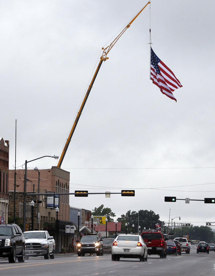Photo -  Left: The flag flies 200 feet into the air over Main Street. PHOTOS BY STEVE SISNEY, THE OKLAHOMAN   STEVE SISNEY -
