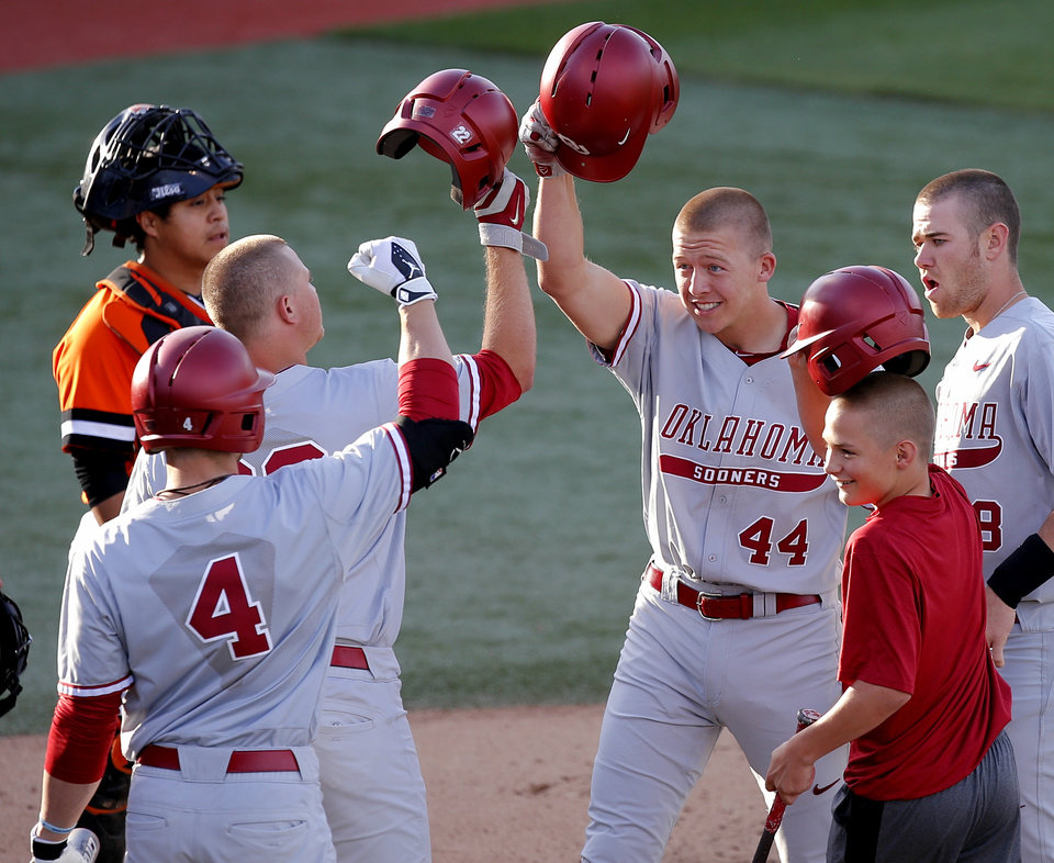 Photo - OU's Austin O'Brien celebrates after scoring on a grand slam as OSU's Robie Rojas watches in the first inning of a Bedlam baseball game between Oklahoma State University and the University of Oklahoma in Stillwater, Tuesday, April 15, 2014. Photo by Bryan Terry, The Oklahoman