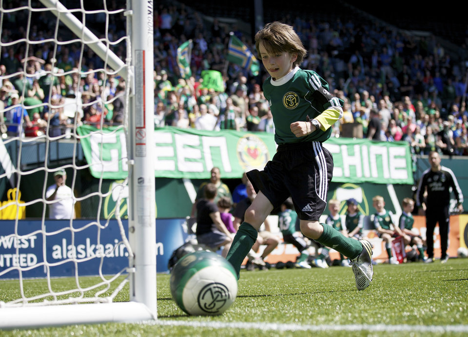 Photo - Atticus Lane-Dupre, 8, heads to the goal as his soccer team, The Green Machine, plays the Portland Timbers soccer team in Portland, Ore., Wednesday, May 1, 2013. The Timbers and Make-A-Wish Oregon treated Atticus' team to a game at Jeld-Wen Field with more than 3,000 fans coming out to lend their support. Atticus missed the Green Machine's final match last fall because of cancer treatment. (AP Photo/The Oregonian, Bruce Ely)