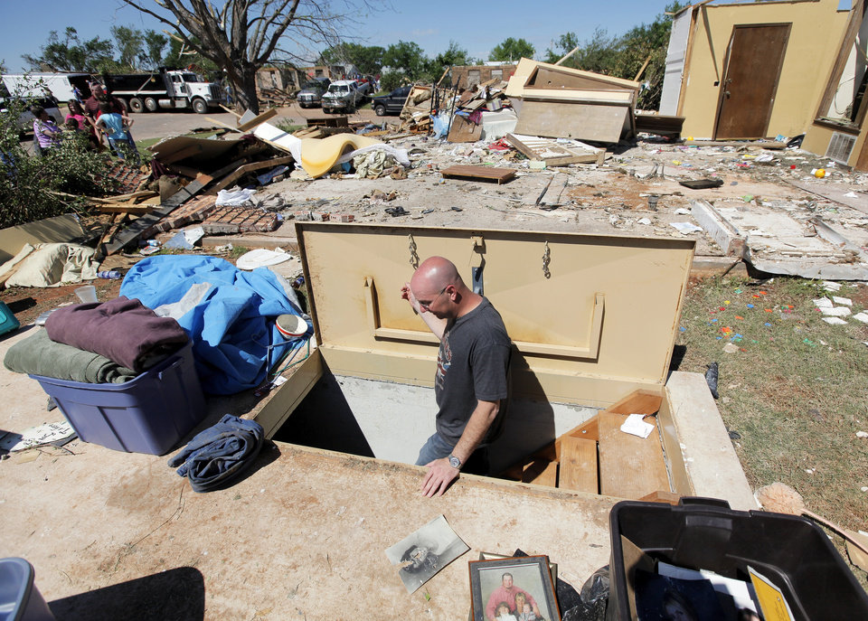 Photo - Gerald Newby walks down into the storm cellar at the home of his mother, Debbie Whisennand, and step-father, Tom Whisennand, to collect valuables that have been stored in the cellar while cleaning up what is left of the home in Woodward, Okla., Monday, April 16, 2012.  The Whisennands took shelter in the storm cellar as a tornado struck the town early Sunday morning. Photo by Nate Billings, The Oklahoman