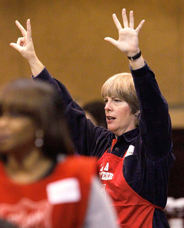 Photo - First-time volunteer Lizz (cq) Foxhoven raises her hands to indicate she has a table available for seven brunch guests. Salvation Army spokesperson Heidi Brandes said more than 1,000 guests were served a hot meal at the  Thanksgiving brunch by volunteers in the Coca-Cola Bricktown Events Center .Thursday morning,  Nov. 24, 2011.  Diners were served eggs, sausage, hash brown potatoes, biscuits and gravy, juice and coffee. Donuts, donated by Krispy Kreme, were also offered to guests. Photo by Jim Beckel, The Oklahoman   Photo by Jim Beckel, The Oklahoman