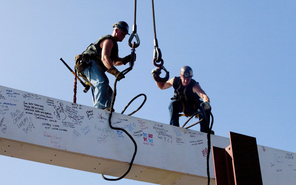 Photo - FILE - In this file photo of Aug. 2, 2012, ironworkers James Brady, left, and Billy Geoghan release the cables from a steel beam after connecting it on the 104th floor of One World Trade Center in New York. The beam was signed by President Barack Obama with the notes: