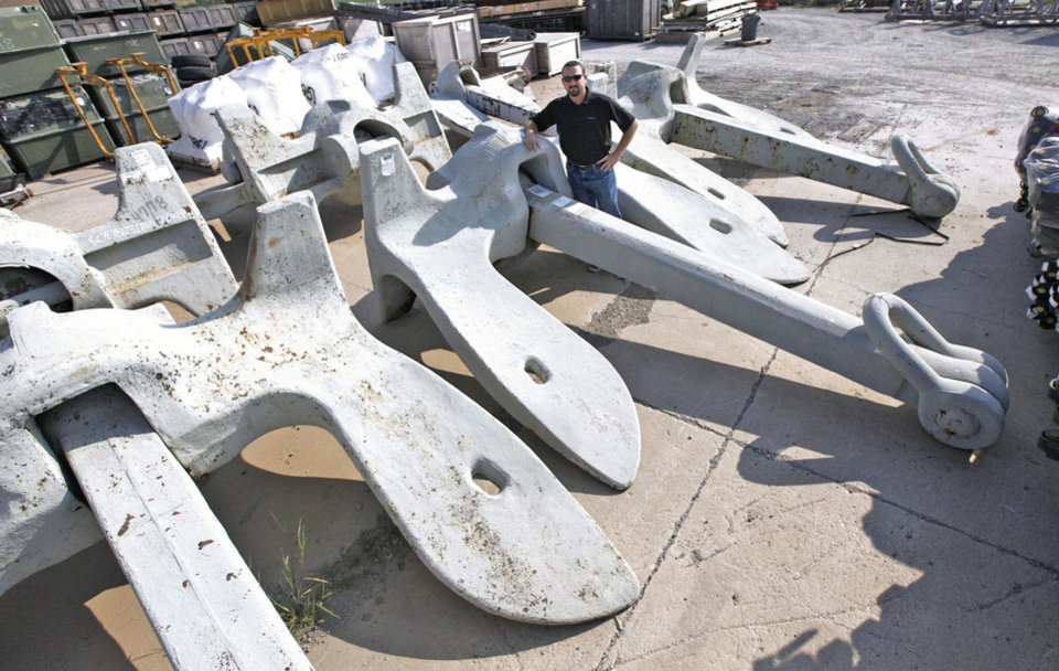 Photo - Government Liquidation warehouse Director Stephen Jackson stands beside the Navy ship anchors being auctioned. They weigh 35,000 pounds each, are 16.7 feet long, 13 feet wide and made of steel.  PAUL HELLSTERN - The Oklahoman