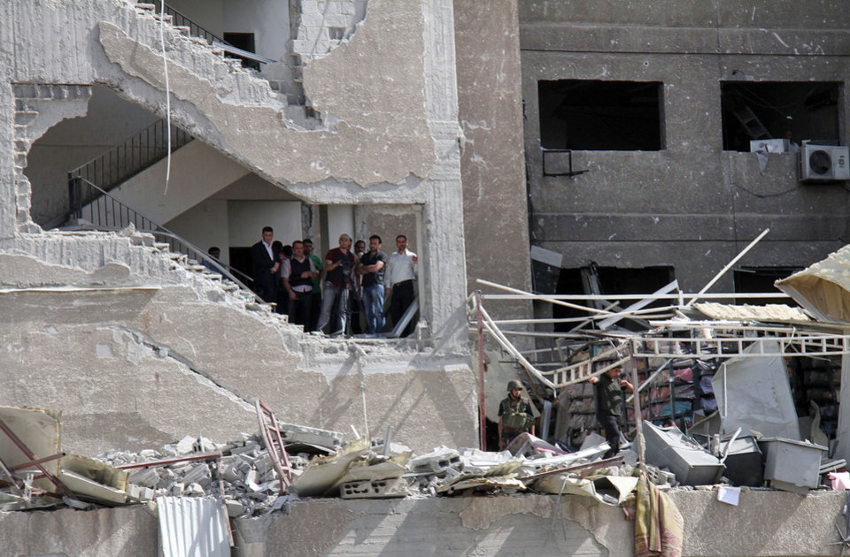 Photo - Syrian security officers stand inside a damaged military intelligence building where two bombs exploded, at Qazaz neighborhood in Damascus, Syria, on Thursday May 10, 2012. Two strong explosions ripped through the Syrian capital Thursday, killing or wounding dozens of people and leaving scenes of carnage in the streets in an assault against a center of government power. (AP Photo/Bassem Tellawi) ORG XMIT: BEI117
