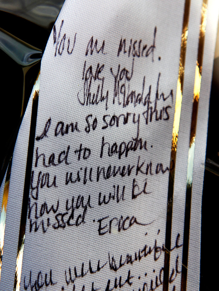Photo - Hand written notes on a wreath hanging in the window of  her family's fitness center in Elgin, pay tribute to murder victim Barbara Diane Dye.  Residents of Elgin Okla, react Tuesday, July 20, 2010, to yesterday's  shooting death of local teacher  Barbara Diane Dye at the hand of her husband,  Raymond Lee Dye, 42, in the parking lot of a bank in this southwest Oklahoma community of about 1400 people just north of Lawton.     