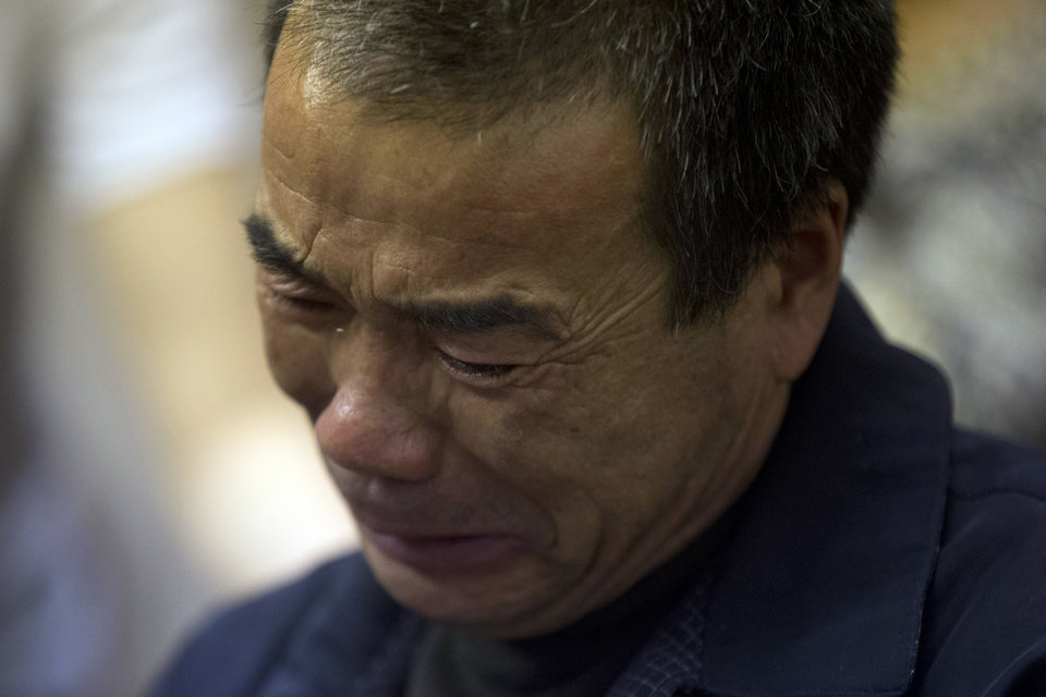Photo - Feng Zhishang cries as family members mark the birthday of his son Feng Dong, a passenger onboard the Malaysia Airlines flight MH370 at a hotel where relatives gather to wait for news of the missing plane in Beijing, China, Tuesday, April 8, 2014. Search crews have failed to relocate faint sounds heard deep in the Indian Ocean, possibly from the missing Malaysian jetliner's black boxes whose batteries are at the end of their life. (AP Photo/Ng Han Guan)