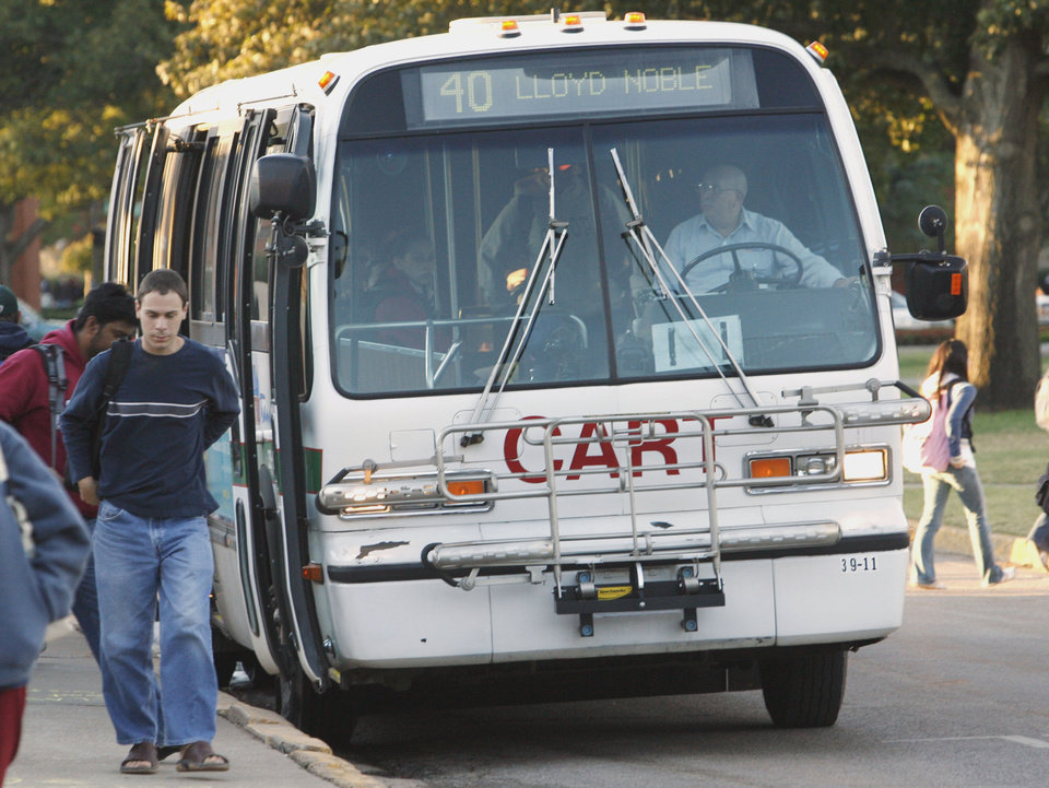 Photo - OU, METRO TRANSIT BUS, CART BUS SYSTEM: Metro Transit busses pick up and drop off passengers on the South Oval of the University of Oklahoma campus on Wednesday, Oct. 24, 2007, in Norman, Okla.  By STEVE SISNEY, The Oklahoman  ORG XMIT: KOD