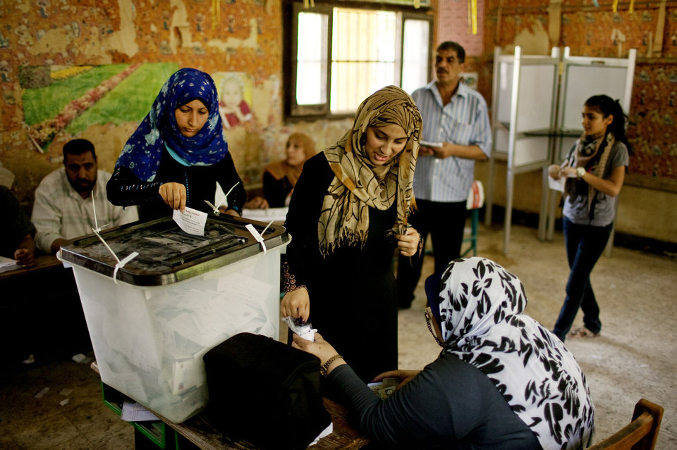 Photo -   Egyptian women vote at a polling station in Shubrah El-Kheima, a working class, industrial area on the outskirts of Cairo, Egypt on Saturday, June 16, 2012. Egyptians voted Saturday in the country's landmark presidential runoff, choosing between Hosni Mubarak's ex-prime minister and an Islamist candidate from the Muslim Brotherhood after a race that has deeply polarized the nation. The two-day balloting will produce Egypt's first president since a popular uprising last year ousted Mubarak, who is now serving a life sentence. (AP Photo/Pete Muller)