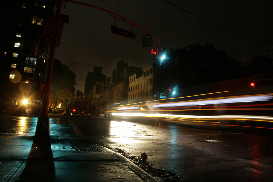 Photo -   Cars pass through a darkened neighborhood on the west side of Manhattan on Monday, Oct. 29, 2012 in New York. Much of New York was plunged into darkness Monday by a superstorm that overflowed the city's historic waterfront, flooded the financial district and subway tunnels and cut power to hundreds of thousands of people. (AP Photo/Peter Morgan)