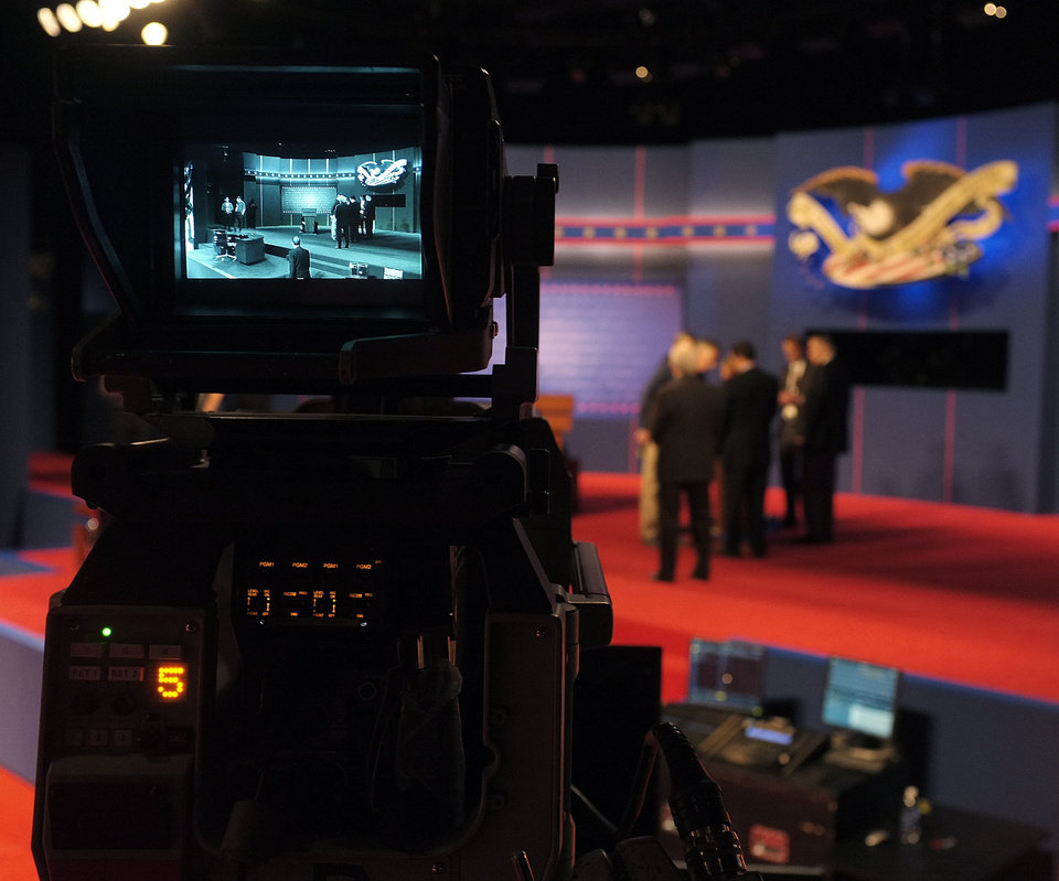 Photo -   Last minute stage setup for the first Presidential Debate between President Barack Obama and Republican presidential nominee Mitt Romney at the University of Denver take place as seen in a television camera monitor Wednesday, Oct. 3, 2012, in Denver. (AP Photo/J. David Ake)