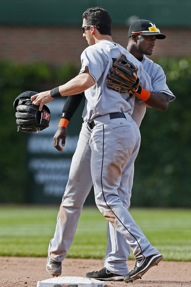 Photo - Miami Marlins shortstop Adeiny Hechavarria, rear, and second baseman Ed Lucas celebrate after defeating the Chicago Cubs 4-3 in a baseball game on Sunday, June 8, 2014, in Chicago. (AP Photo/Andrew A. Nelles)