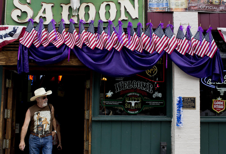 A man walks out of Matt's Saloon, which is decorated with with 19 United States flags topped with purple ribbons and bunting, along Whiskey Row, Friday, July 5, 2013 in Prescott, Ariz.  The flags and ribbons were hung in honor of the 19 fallen Granite Mountain Hotshot firefighters who died battling a blaze near Yarnell, Ariz. on Sunday. (AP Photo/Julie Jacobson)
