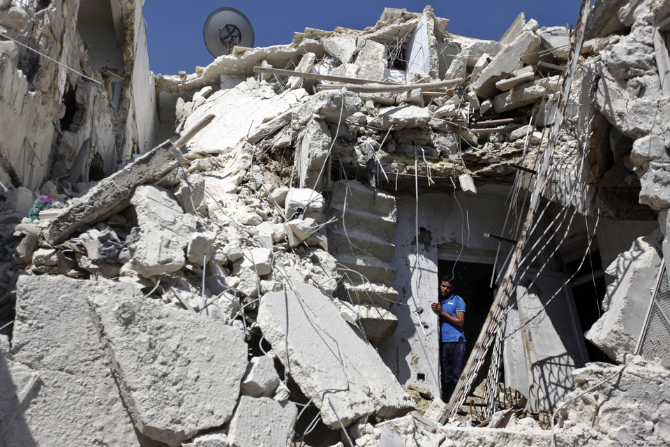 Photo -   A Syrian man looks out of the rubble as rescuers, not shown, look for the bodies of two girls thought to be under the rubble of a building hit by a Syrian government airstrike in Aleppo, Syria, Sunday, Aug. 19, 2012 (AP Photo/ Khalil Hamra)