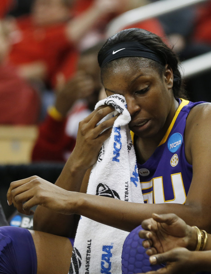 Photo - LSU forward Shanece McKinney (21) wipes her eyes as she sits on the bench in the final moments of a 73-47 loss to Louisville in a regional semifinal game at the NCAA college basketball tournament on Sunday, March 30, 2014, in Louisville, Ky. AP Photo/John Bazemore)