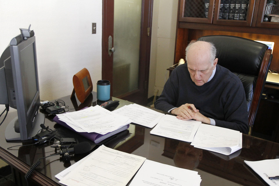 Photo - Left: Special Judge  Russell Hall looks over court documents  Monday before the video arraignment of homicide suspect Justin Adams.  Photo by Steve Gooch,  The Oklahoman
