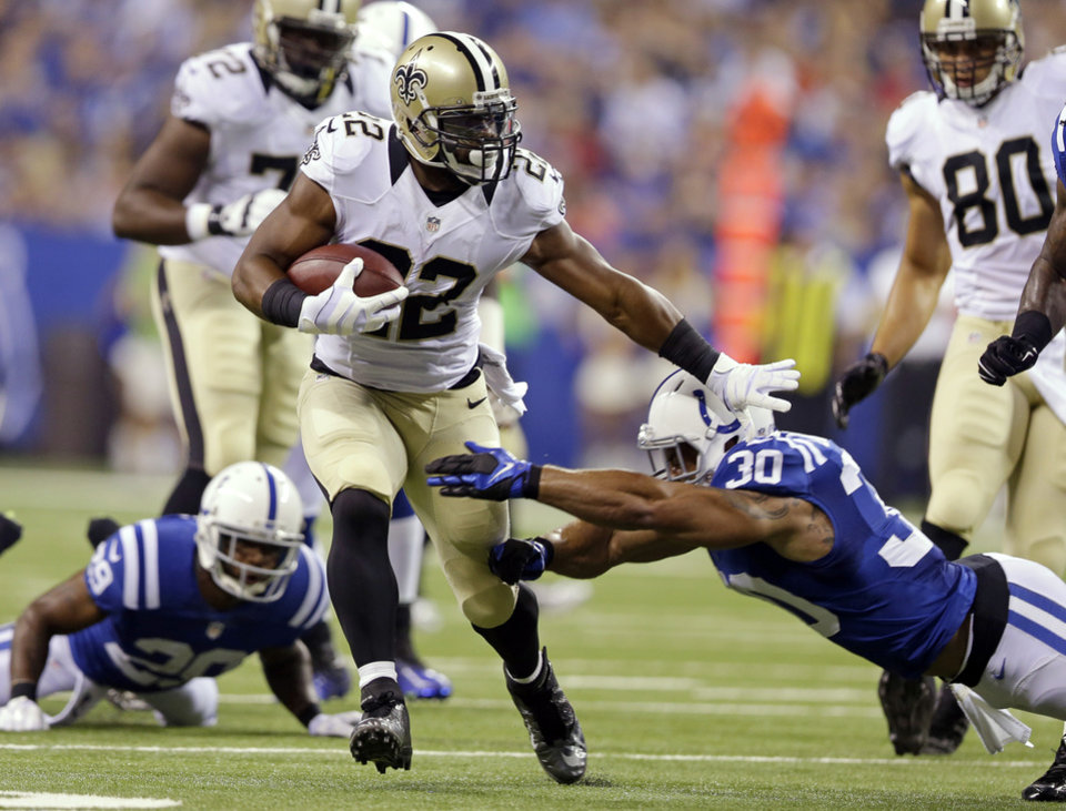 Photo - New Orleans Saints running back Mark Ingram breaks the tackle of Indianapolis Colts strong safety LaRon Landry (30) during the first half of an NFL preseason football game in Indianapolis, Saturday, Aug. 23, 2014. (AP Photo/Michael Conroy)